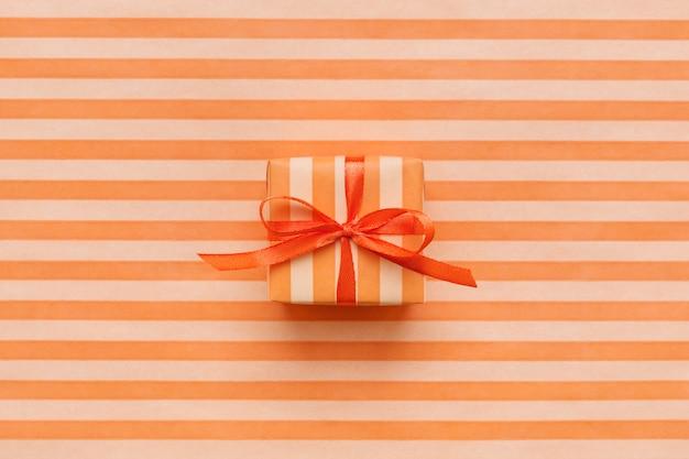 ストライプの包装紙にオレンジ色のギフトボックス。