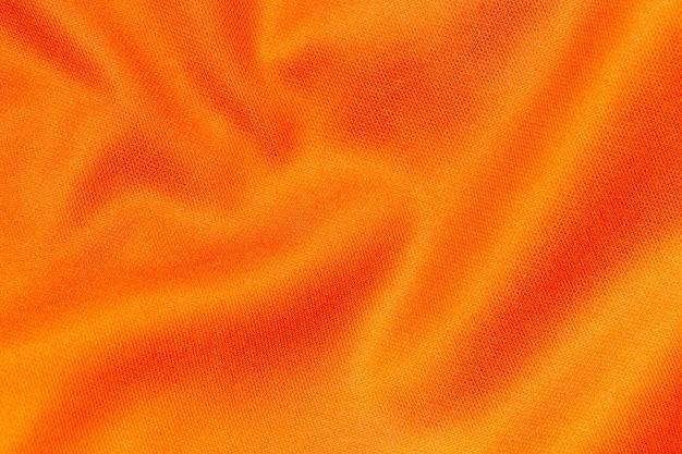 Оранжевый цвет спортивной одежды ткань футбольная рубашка джерси текстуры и текстильный фон.