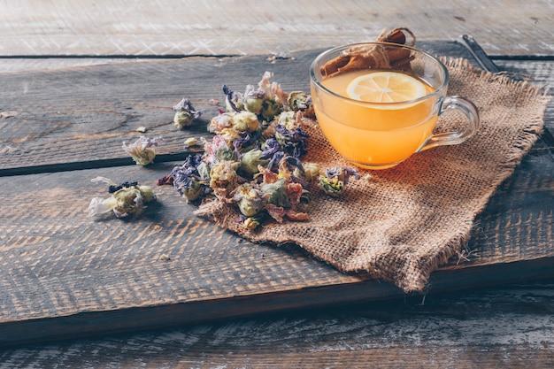 Вода оранжевого цвета в чашке с лимонным и чайным видами под высоким углом на мешковиной ткани и темном деревянном фоне