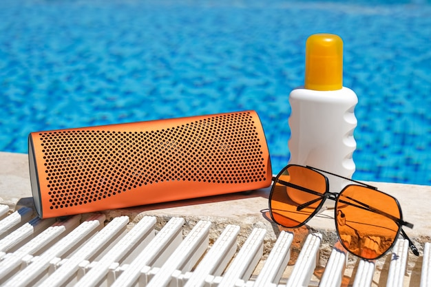 Orange coloured beach accessories near swimming pool. sun cream, sunglasses, music bluetooth speaker.