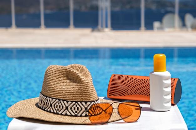 スイミングプールの近くのオレンジ色のビーチアクセサリー。日焼け止め、サングラス、音楽スピーカー、麦わら帽子。