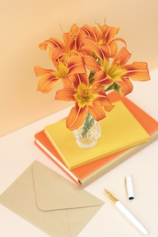 orange composition with flowers and notebooks