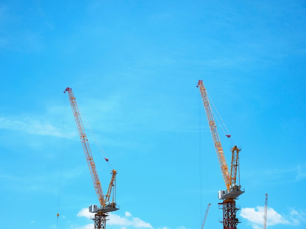 Orange construction cranes with boom structure pointing up against blue sky