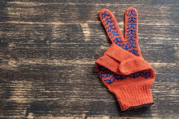 オレンジの建設用手袋は木製の勝利のサインを示しています