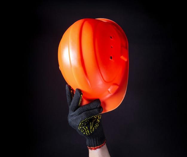 오렌지 건설 헬멧 클로즈업입니다. 남자는 주황색 건설 헬멧으로 인사 제스처를 만듭니다.
