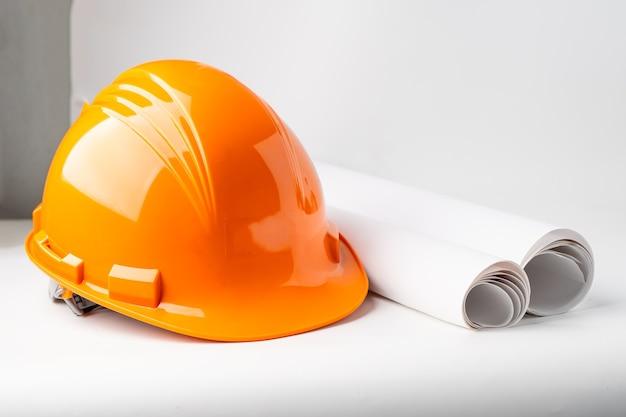 白い背景、エンジニアの概念に分離されたオレンジ色の建設ヘルメット。