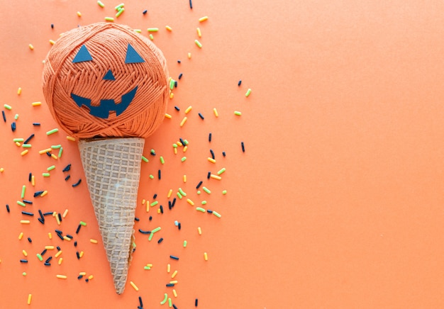 Orange cotton ball forming a halloween pumpkin with ice cream cone and sugar sprinkles on orange