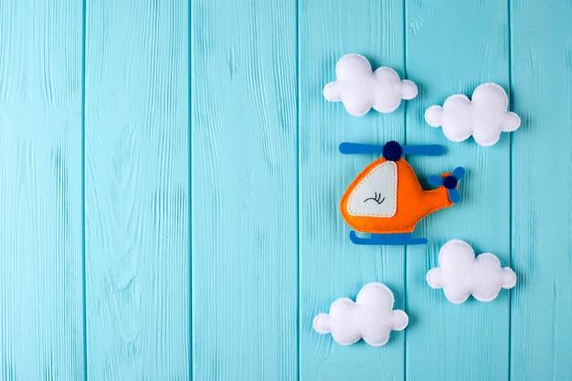 Оранжевый вертолет и облака ремесла на голубой деревянной предпосылке с copyspace. войлочные игрушки ручной работы.