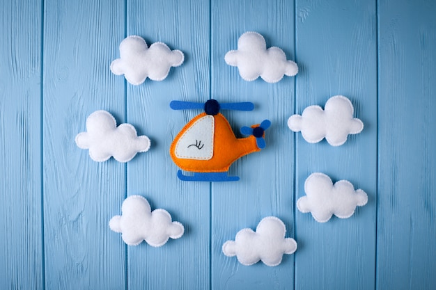 Orange craft helicopter and clouds on blue wooden background with copyspace. felt handmade toys.