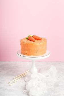 Апельсиновый кремовый торт с двумя мастичными морковками на праздник, розовый фон, вертикальный формат