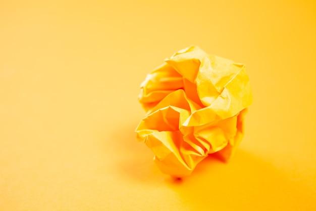 橙色弄皱的纸在橙色表面上