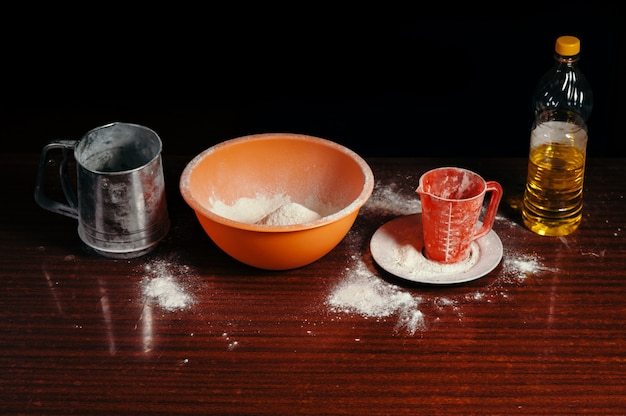 Orange cup, measuring cup and steel sieve, sunflower oil stand on wooden table on black scene