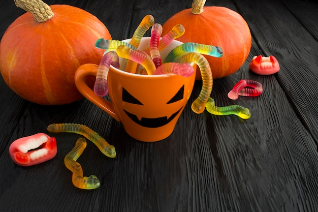 Orange cup with candy for halloween and pumpkins beside