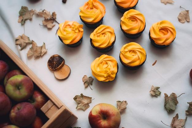 秋の乾燥した葉とリンゴのオレンジ色のカップケーキ