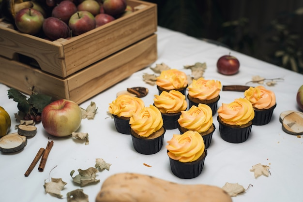 秋の乾燥した葉、カボチャ、リンゴとオレンジ色のカップケーキ