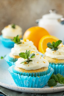 Orange cupcakes with curd cream on the christmas festive table copy space