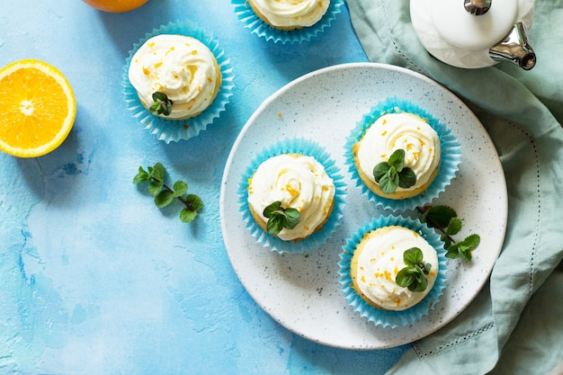 Orange cupcakes with curd cream on the christmas festive table top view flat lay background