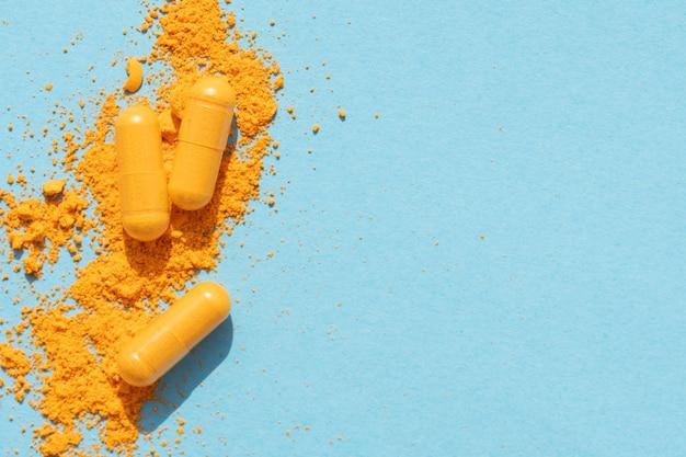 Таблетки куркумы оранжевого цвета с порошком и тенью на синем фоне