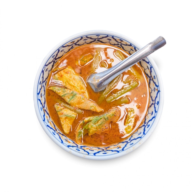 Orange curry with cha-om isolate on white background