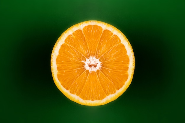 Orange cut in half against green background