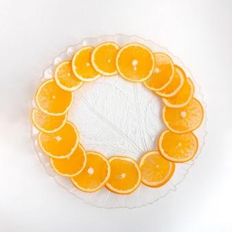 An orange cut into circles lies on a transparent plate.