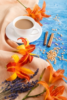 Orange day-lily and lavender flowers and a cup of coffee on a blue concrete background