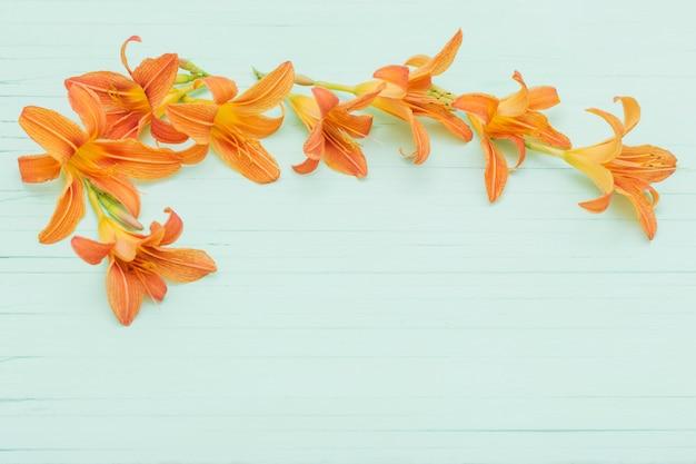 木製の背景にオレンジ色のユリ