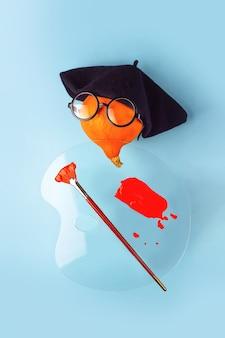 黒いベレー帽のオレンジ色の装飾的なカボチャアーティスト