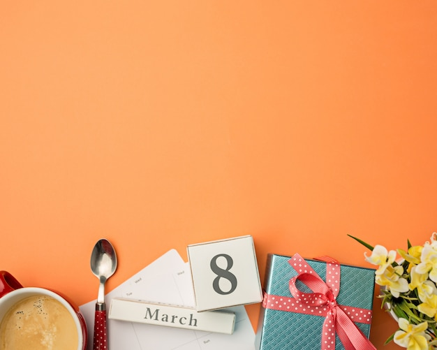 Orange desk with cup of coffee, gift, flowers and notebook