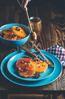 ワインの蜂蜜またはメープルシロップとジンジャースパイスのオレンジデザート、ザクロの果実が飾られています。驚くほど甘く、リッチでフレッシュな料理。暗い素朴な背景、テキストのコピースペース