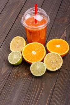 Оранжевый коктейль детокс с половиной апельсина, лимон и лайм лежат на столе