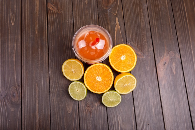 Orange detox coctail with half orange,lemon and lime lies on table