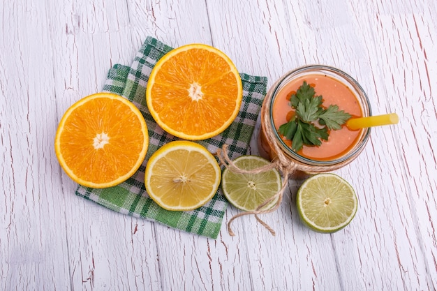 Orange detox coctail with half orange and lime lies on table