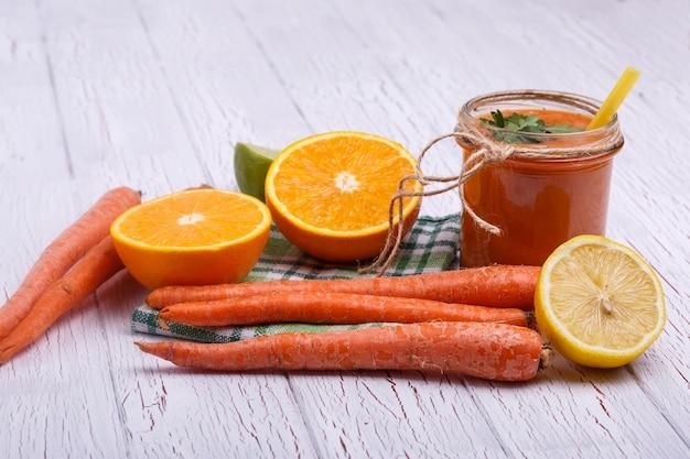 オレンジ色のデトックスカクテル、オレンジとニンジンと白いテーブルに横たわる