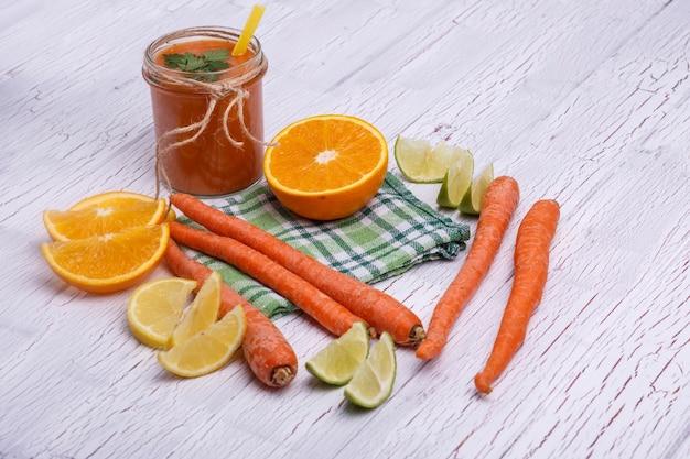 Апельсиновый коктейль детокс с апельсинами и морковью лежит на белом столе