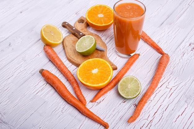 Апельсиновый коктейль детокс с апельсинами, лаймом и морковью лежит на белом столе