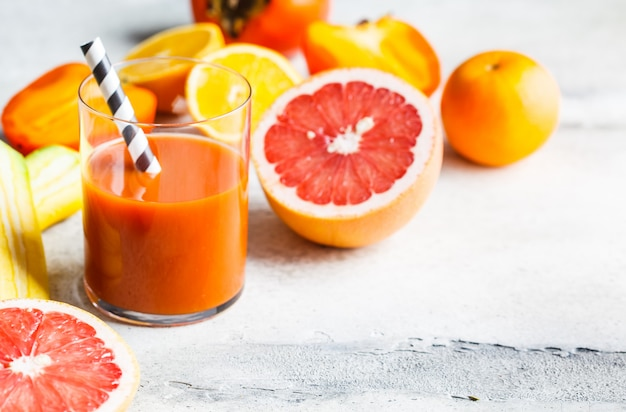 Orange detox juice in a glass and ingredients for smoothie background.