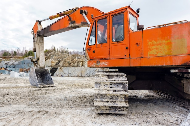 Orange dirty excavator stands in a quarry for the extraction of marble