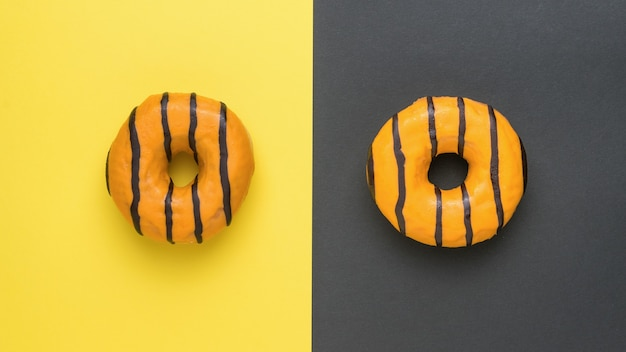 黄色と黒の背景にチョコレートで艶をかけられたオレンジ色のドーナツ。おいしい人気のペストリー。