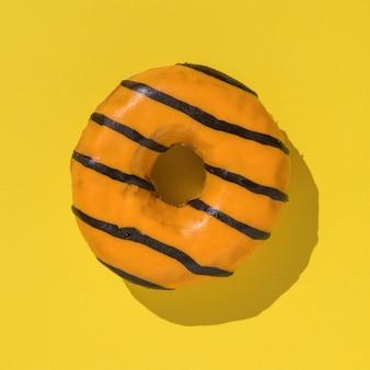 黄色の表面に明るい光の中でオレンジ色のドーナツ