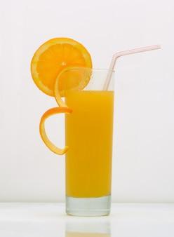 Апельсиновый напиток в стакане с долькой грейпфрута и соломкой. напиток на белом фоне