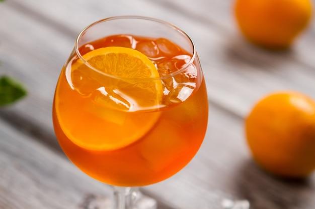와인잔에 오렌지 음료입니다. 얼음과 오렌지 조각. 수입 와인을 곁들인 아페롤 스프릿츠. 파티를 즐기세요.