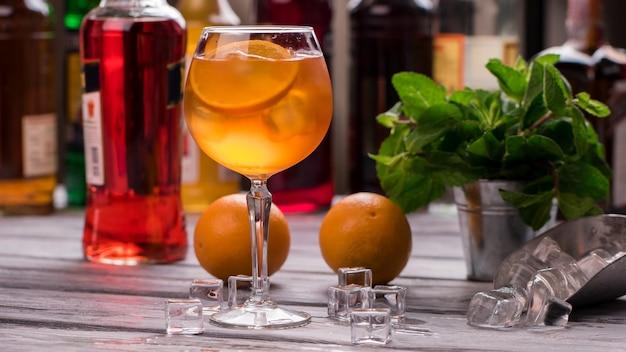 와인잔에 오렌지 음료입니다. 얼음 조각과 오렌지. aperol spritz의 조리법. 우리 바에서 가장 맛있는 칵테일.