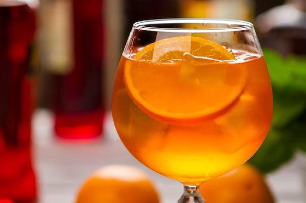 와인잔에 오렌지 음료입니다. 과일과 얼음 조각. 식힌 아페롤 스프릿츠. 드라이 와인과 소다수.