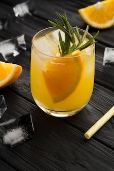 Апельсиновый напиток или лимонад с розмарином и льдом в стакане на черном деревянном фоне. крупный план. расположение вертикальное.