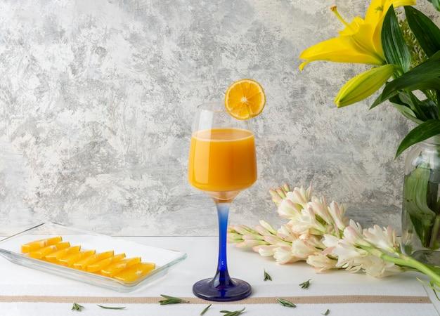 테이블에 조각과 꽃병이 있는 크리스탈 유리에 제공되는 오렌지 음료 프리미엄 사진