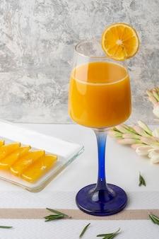 テーブルの上にスライスと花瓶が付いたクリスタルガラスで提供されるオレンジ色の飲み物