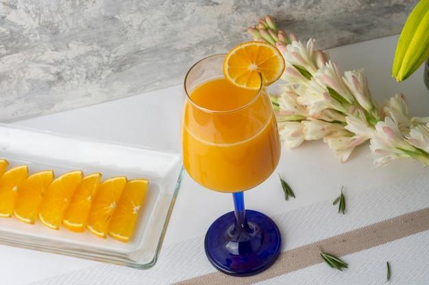 테이블에 조각과 꽃병이 있는 크리스탈 유리에 제공되는 오렌지 음료