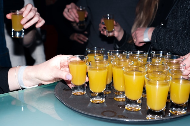 Orange drink in shot glasses with hands - party in bar