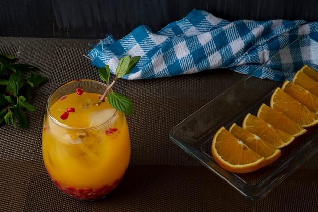 Апельсиновый напиток с мятой, льдом и гранатом на коричневом столе с дольками апельсина на тарелке